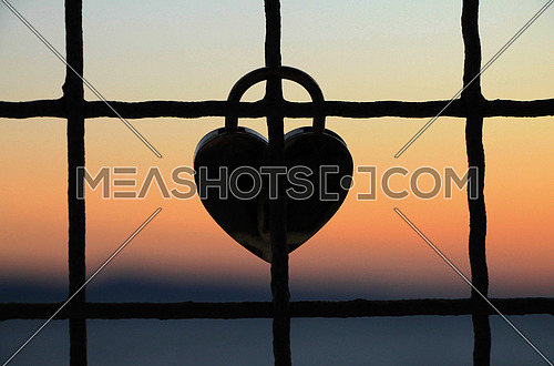 Heart shape padlock at sunset on fence