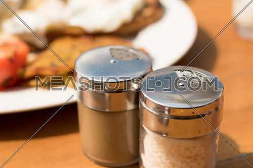 Salt and Pepper shakers on a wooden breakfast table