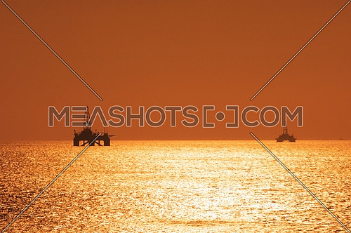 Two offshore oil rigs during sunset  in Caspian sea