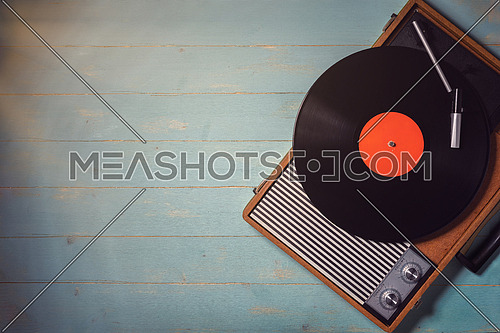Old record player from the 70s with a vinyl record on green wooden table, top view and copy space.