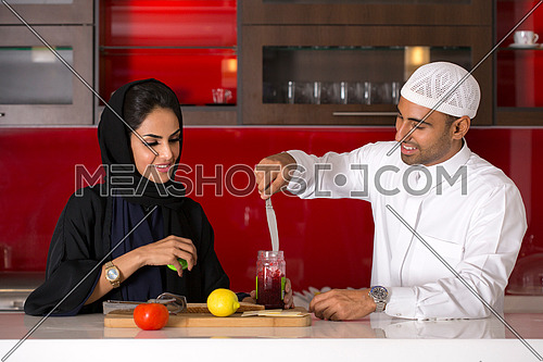 Couple in Saudi tradition clothes Focusing in the working together in the Kitchen.