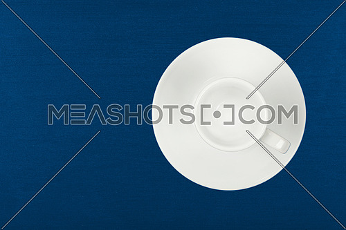 Close up one empty white espresso coffee cup on saucer over dark blue table background, elevated top view, directly above
