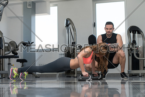Personal Trainer Takes Notes While Young Woman Exercise Push-Up Strength In A Gym
