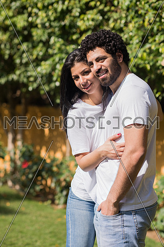 Young Middle Eastern couple enjoying the beautiful summer day in the garden with a smile and happiness