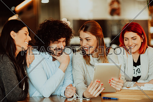A group of friends hanging out in a cafe, and among them is a tablet. Happy young people sitting in a restaurant using tablets