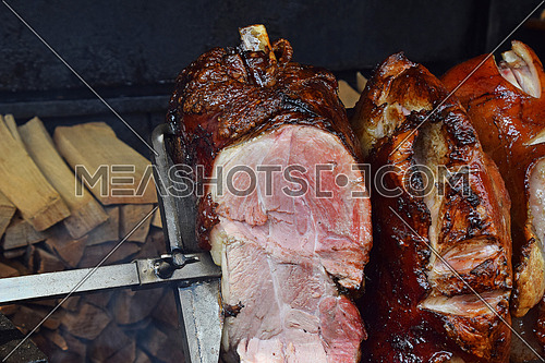 Close up several big pieces of pork ham meat rotating to be evenly roasted on open wood fire skewer, high angle view