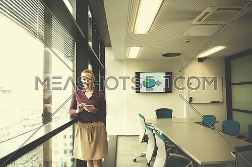 yonug businesswoman in casual hipster clothes using smart phone  at modern startup business office meeting room  interior
