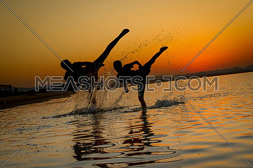 An adult and a young boy training for Marshal arts in a shallow sea during sunset