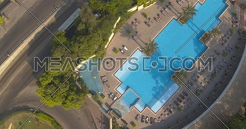 Lift of shot for drone over The Nile Ritz Carlton Hotel pool while two people are swimming at day time