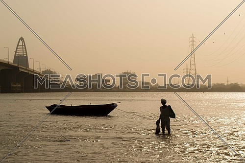 A silhouette of a fisherman against the Skyline of the city of Khartoum, SUDAN