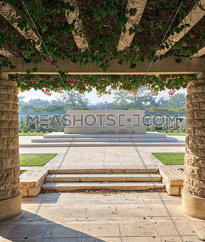 Entrance of Heliopolis Commonwealth War Cemetery with two stone bricks columns and climber green plants, Cairo, Egypt