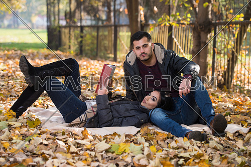 Beautiful Young Couple Sitting In The Park On A Beautiful Autumn Day - They Are Reading A Book