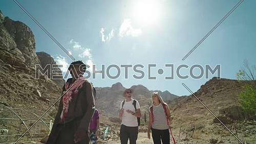 Track in shot for group of tourists sitting with bedouin guides exploring Sinai Trail from Ain Hodouda at day.