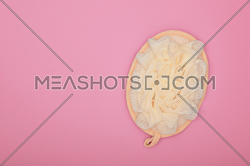 Close up one feminine soft bath shower skin scrub puff over pink background, elevated top view, directly above