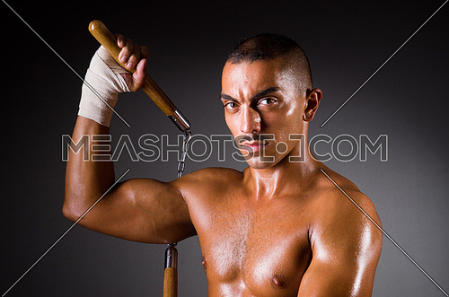 Muscular man with nunchucks on a dark background