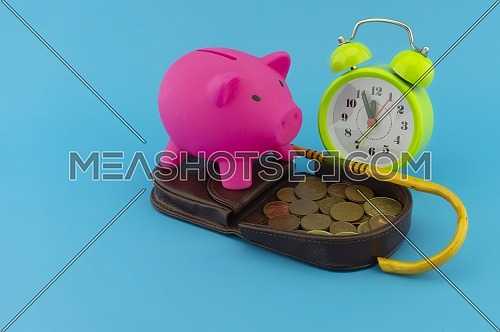 Saving for old-age and retirement concept with open purse with coins, walking stick, alarm clock and piggy bank over a blue background with copy space