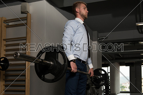 Young Business Man Doing Heavy Weight Exercise For Back In Gym
