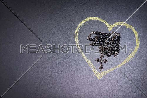 in the picture a rosary iron at the center of a heart drawn with a crayon and copy space in the left side.