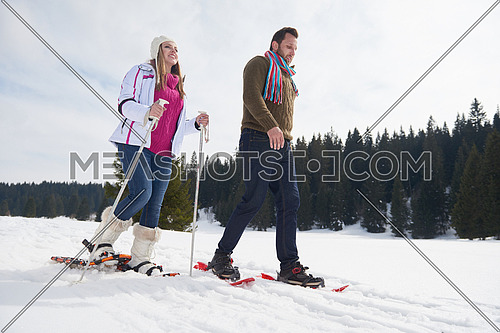 happy young  couple having fun and walking in snow shoes outdoor in nature at beautiful winter day. Health sport and relaxation
