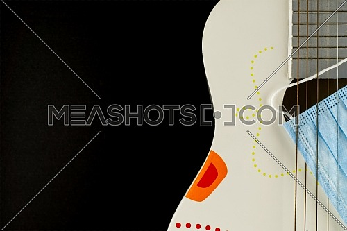 Wooden acoustic guitar body and a face mask between the strings over a black background with free space for text