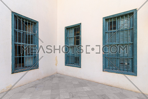 Corner white wall with three grunge windows with wooden green shutters and wrought iron bars and tiled white marble floor