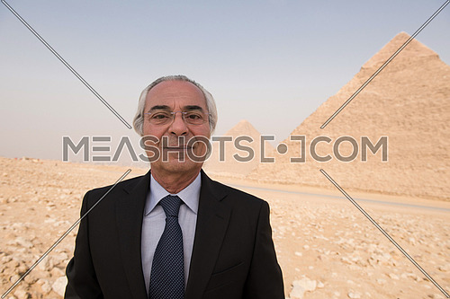 portrait of mature middle eastern business man in front of ancient egyptian pyramids