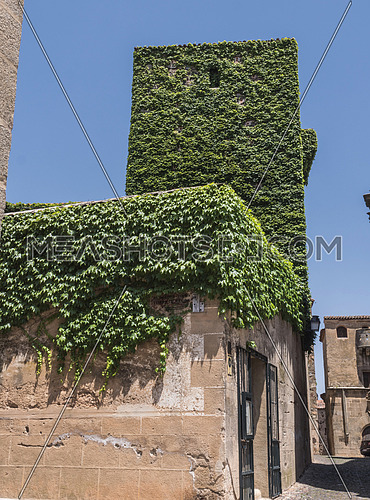 Caceres, Spain - july 13, 2018: House of the walls-Saavedra and tower of Sande, is Gothic, of the 14th century, rebuilt in the 15th century, square of San Mateo, Caceres, Spain