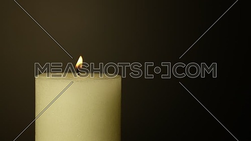 Close up one white candle trembling flame out of the dark over black background, off-center, fired up with lighter, burning and blown out