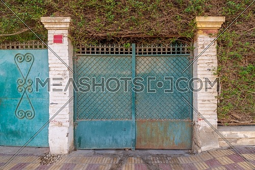 Background of green old weathered grunge antique wrought iron gate with geometrical pattern ornaments between two white bricks columns