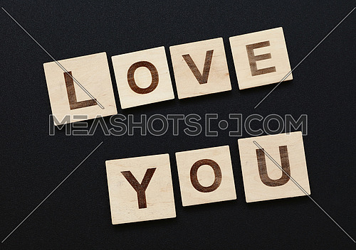 Close up words LOVE YOU on wooden letter signs over black board background