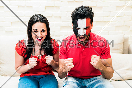 young couple cheering for egypt sitting on a sofa and the male has egyptian flag paint on his face while showing the exciting about the match