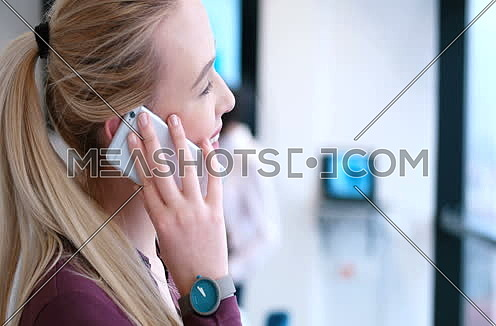 Elegant Blond Woman Using Mobile Phone in office interior