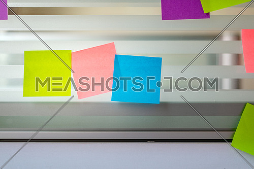 Randomly scattered blank colored sticky notes over glass screen of a bench desk