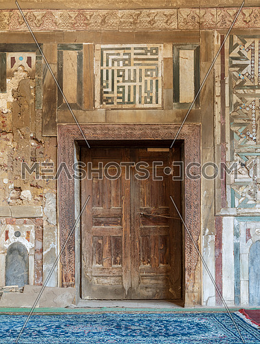 Grunge wooden decorated door on external old decorated marble wall, El Mardani Mosque, Cairo, Egypt