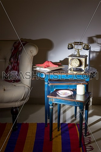 Interior shot of old golden telephone set, white candle, red starfish and colorful ornate plate over three nested tables with blue legs over off white wall, and cream armchair with harsh light