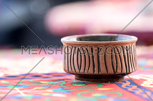 Potter over a table covered by oriental table clothe