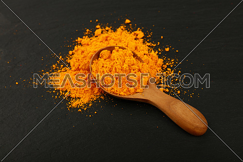 Close up one wooden scoop spoon full of yellow turmeric powder spice on background of black slate board, high angle view