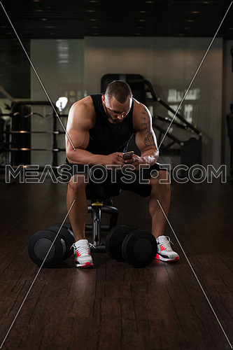 Bodybuilding Healthy Fitness Man Using Smartphone While Resting In The Gym