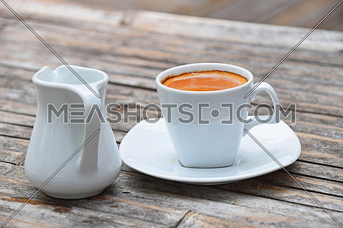 One white cup full of espresso coffee with brown crema on porcelain saucer with small milk jug on old vintage bamboo wooden table