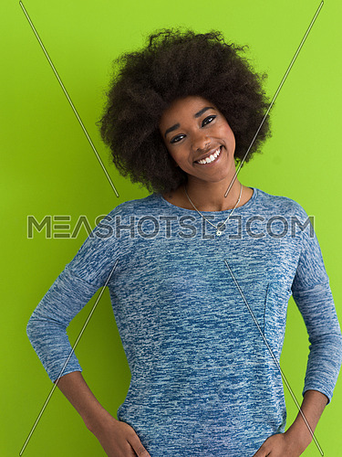 portrait of a beautiful friendly African American woman with a curly afro hairstyle and lovely smile isolated on a Green background