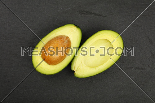 One fresh ripe green avocado cut in two halves with pit stone on black slate board background, detail, close up, elevated top view