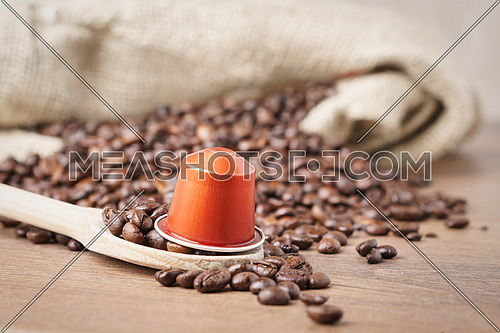 In the foreground a coffee capsule on wooden spoon and  roasted coffee beans with burlap sack on blur wooden background ,close up.