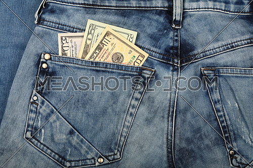 Close up several different value US dollar paper currency banknotes in jeans back pocket, low angle view