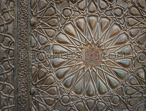 Ornaments of the bronze-plate ornate door of Sultan Barquq mosque, ancient public historic mosque in Old Cairo, Egypt