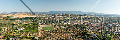 Panoramic view of the Calabrian hinterland, olive fields and wind turbines in the background, Calabria, Italy.