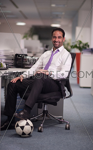 business man at office workplace with  soccer ball under table