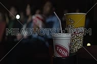 Close Up shot for popcorn and soda containers and young people in the background at movie theatre.
