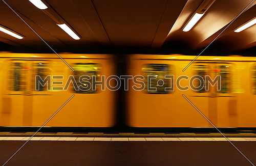 Close up yellow metro underground train carriage in motion, side view