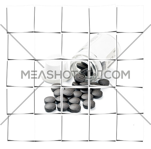 brown pills spilled from glass bottle on white background