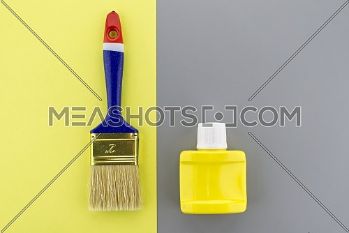 Conceptual image of new clean paintbrush on a two tone grey and yellow background with copyspace viewed as a flat lay. Main color trend of the year 2021